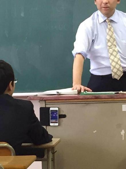 一学生表示,班上有位眼镜兄,哪怕坐在第一排讲桌旁的VIP席,依然能想出办法玩手机游戏……堪称真正的勇者
