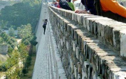 为了逃票,女子徒手爬上城墙