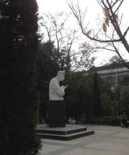 某校的雕塑,远看像是鲁迅在玩手机。