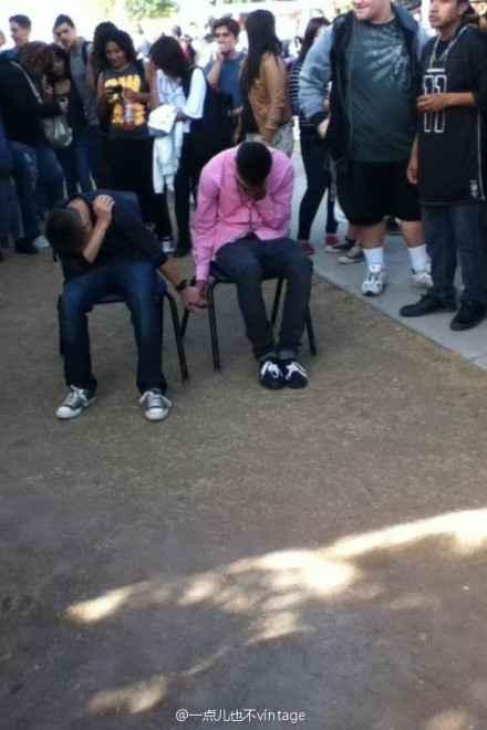 美国Az某校的两名男生在课堂上打架后,校方经研究给了他们两个选择:1.被勒令退学。2:手拉手在学校的院子里坐九天。他们选了这个……