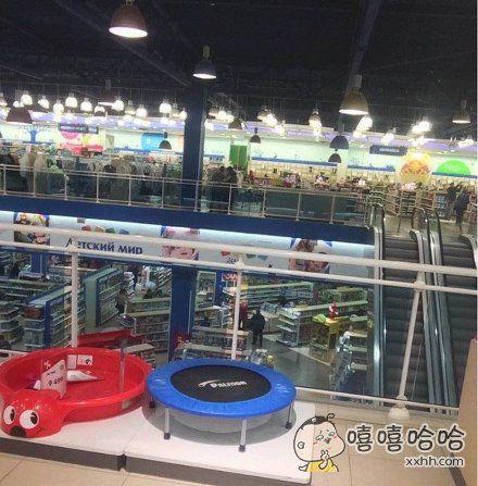 二楼的儿童用品商店护栏边放着一个蹦床,好店家